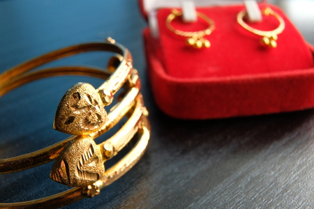 Golden jewellary for new born baby on dark table