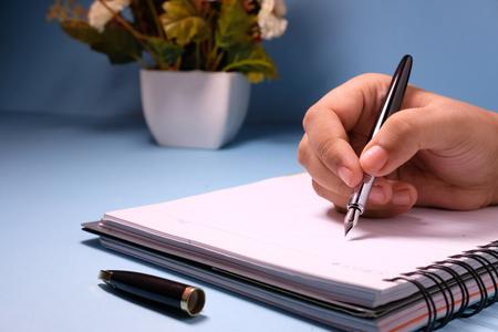 Businesswoman writing in her agenda in er office desk