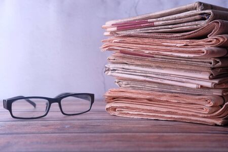 stack of newspaper and eyeglass on table