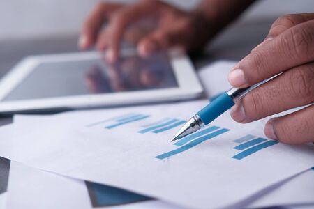 Close up of man analyzing bar chart on paper Banco de Imagens