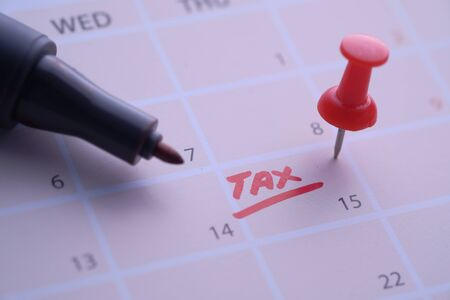 pay tax concept with calendar date and thumbtack