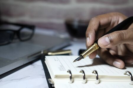 Close up of man hand writing on notepad at office desk. Stock Photo