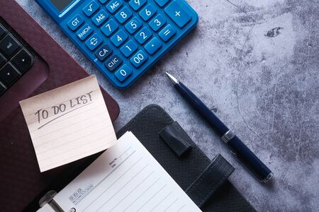 to do list on notepad with laptop and calculator on desk . Stock Photo