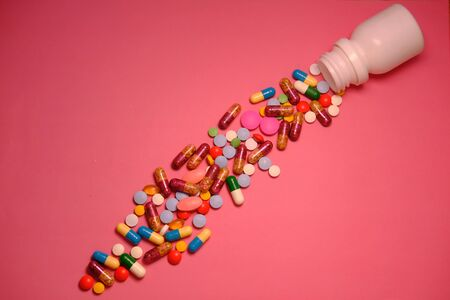 top view of pills and capsule on pink background.