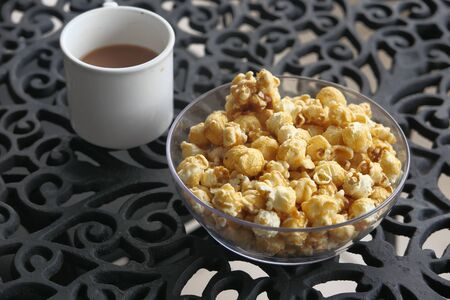 Close up of popcorn in a bowl and tea on table.