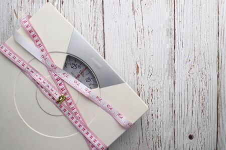 Bathroom scale with measuring tape on wooden background. Weight loss concept