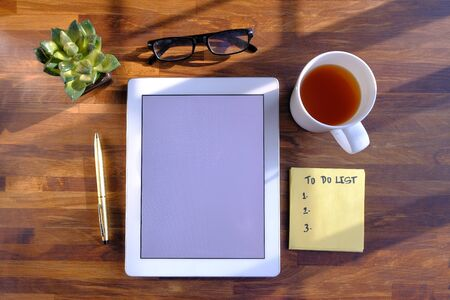 top view of digital tablet, tea and notepad on wooden table