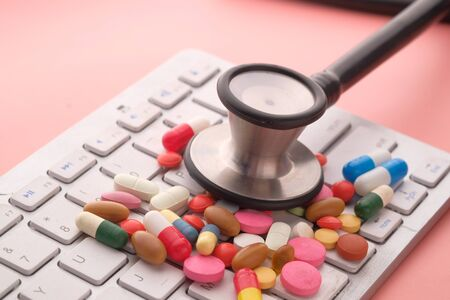 Close up of stethoscope, pills on keyboard Banque d'images - 143291143