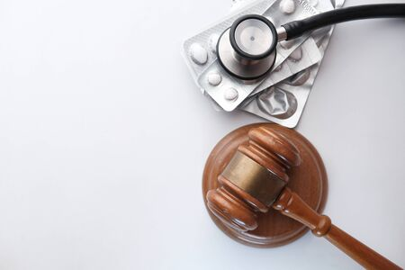 top view of Judge gavel and stethoscope with pills on table Banque d'images - 143291205