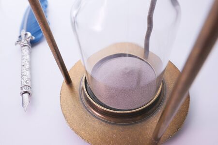 Sand running through the bulbs of an hourglass measuring the passing time