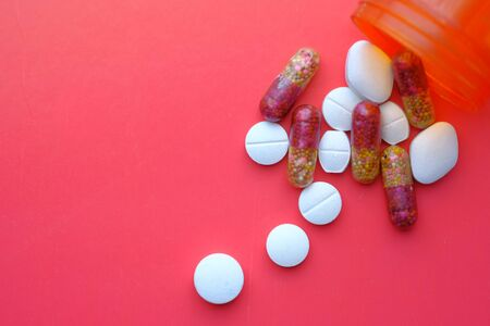 colorful pills pilling from container on red background