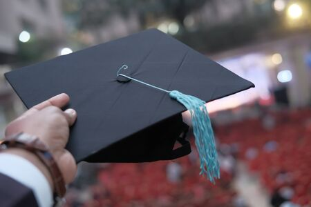 Man hands holding graduation hat outdoor.