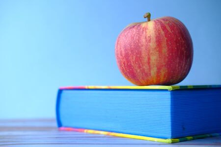 close up of apple on a book on blue background