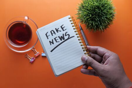 fake news written on notepad, close up,