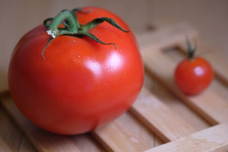 Two red tomatoes on table , small and big.