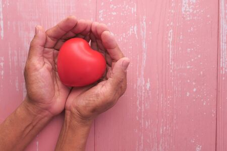 senior woman holding red heart in hands, top view 版權商用圖片