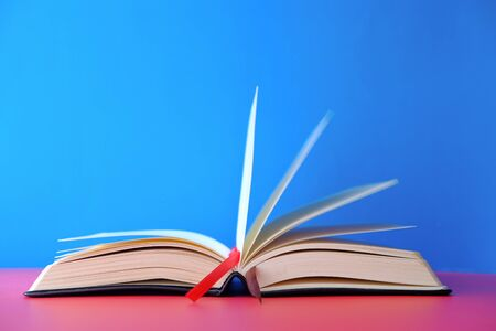Opened empty book on blue background, space for text. Imagens