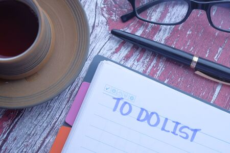 tea cup and notebook with to do list on wooden table