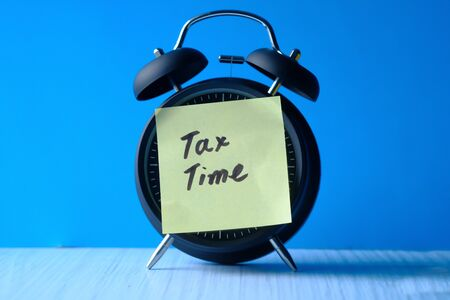 pay tax concept with clock and tax word.