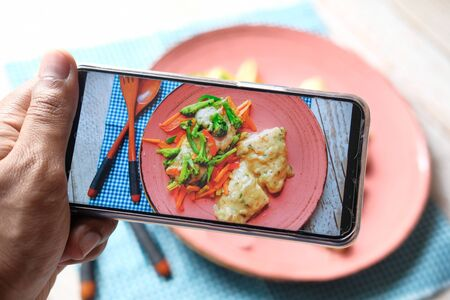 taking photo of fish fillet and salad with smart phone.