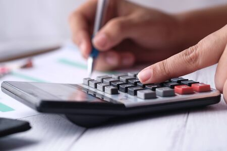 Woman accountant or banker use calculator on table at office