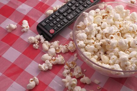 high angel view of popcorn in a bowl and tv remote on table.