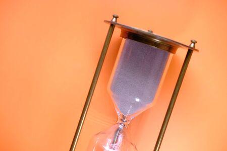 Sand running through the bulbs of an hourglass Imagens