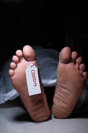 Two feet of a dead body with a tag attached to the toe