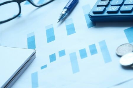 financial charts and office supplies on desk Stock Photo