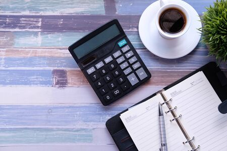 Top view of calculator, notepad and tea on desk Imagens