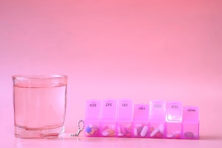 pill box and water glass on pink