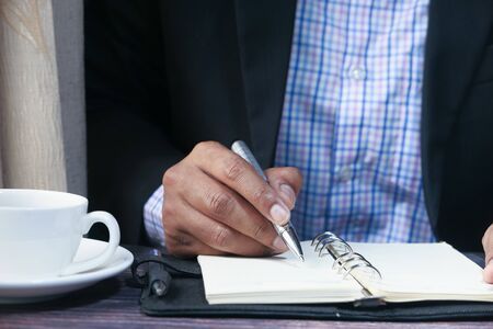 businessman hand writing on notepad, close up Фото со стока