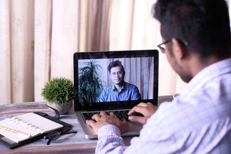Back view of business man in video conference discussing strategy