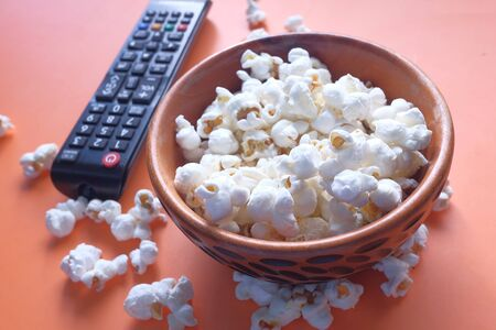 Top view of bowl of popcorn and Tv remote on table