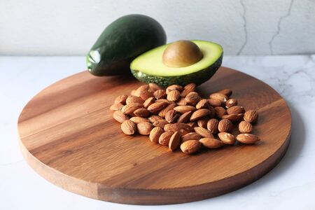 Top view of almond and avocado on chopping board.
