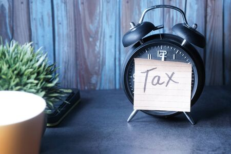 Tax Text on Adhesive Note on Alarm Clock.
