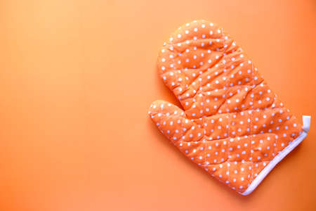 Kitchen gloves on orange background top down.