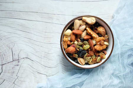 bowl with mixed nuts on white table top down