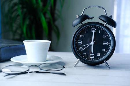 Retro alarm clock, notepad and eyeglass on wood table
