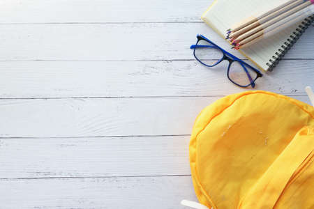 yellow backpack with school suppliers on table with copy space. Reklamní fotografie
