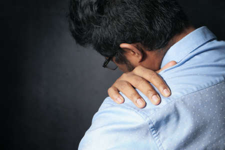 young man suffering shoulder pain isolated on black. Stockfoto