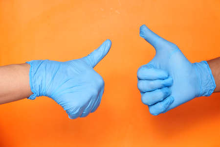 Close-up of a tow people hand in medical gloves showing a thumb-up.