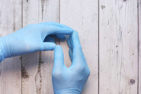 Doctor hand with glove on wooden background. Archivio Fotografico