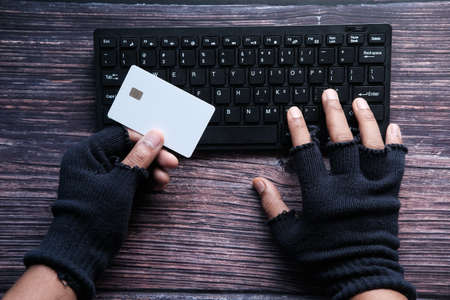 hacker hand stealing data from credit card Foto de archivo