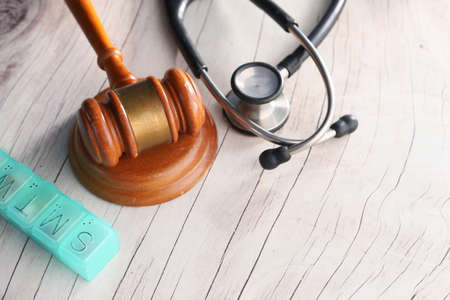 Top view of gavel, stethoscope and pills on white background