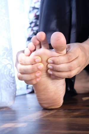 Woman Touching Foot In Pain Close Up.