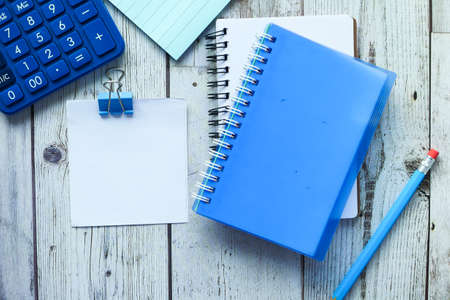 high angle view of notepad and stationary on wooden table