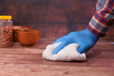 hand in blue rubber gloves cleaning table with cloth Archivio Fotografico