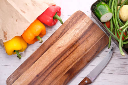 Yellow orange and red capsicum with chopping board on table