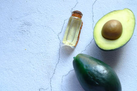 Top view of oil and slice of avocado on wooden table
